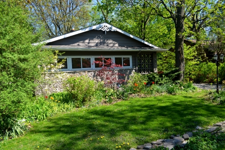 A nice cottage in spring time surrounded by trees in sunshine in Ontario, Canada  photo