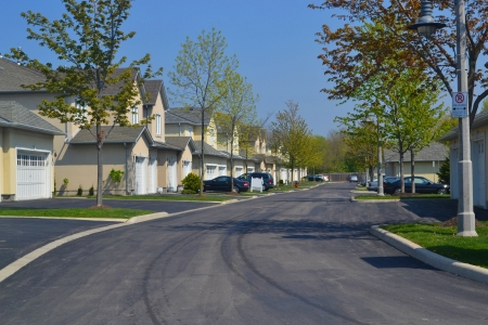 row of houses: A pretty and quiet suburban neighbourhood in the early spring, on a beautiful sunny day  Stock Photo