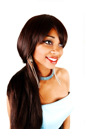 A closeup portrait of a smiling black woman with her beautiful long brunettehair, in a blue dress with blue necklace for white background  Stockfoto