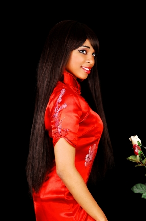 A lovely young black woman in a red chinese dress for black backgroundin profile with her long brunette hair  photo