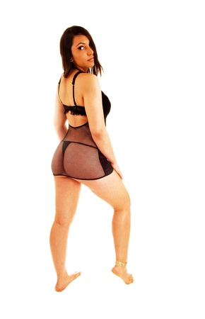 A young woman standing in black lingerie from the back, looking overher shoulder, bare foot for white background  photo