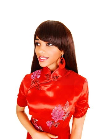 A lovely young black woman in a red Chinese dress standing in a portrait picture for white background. photo