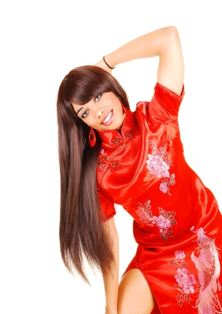 A beautiful young woman in a long red Chinese dress standing for white background, showing her gorgeous long brunette hair.