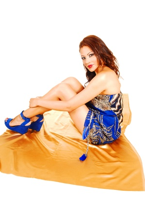 A young pretty woman in a short blue summer dress and high heelssitting on gold fabric on the floor in profile for white background  photo
