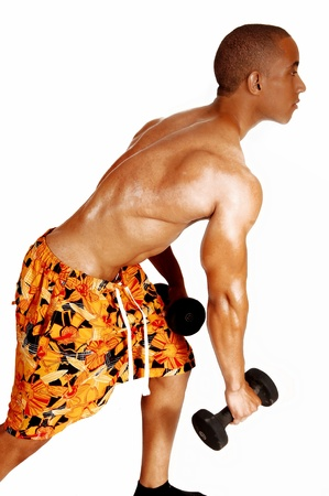 jamaican man: A young Jamaican man in colorful shorts standing in profile for white background, exercising with his black dumbbells.  Stock Photo