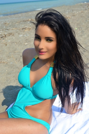 A lovely teen girl in a turquoise bikini sitting on the beach on lake Ontariowith her long black hair, sunbathing, in a closeup picture  photo
