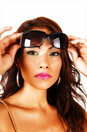 A closeup face shoot of a pretty face of a native Canadian woman withbig earrings and red lips, holding her sunglasses on her forehead  Stock Photo - 20830218