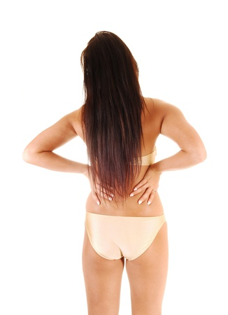 A young teen girl in a gold colour bikini standing from the back with long brunette hair for white background.  photo