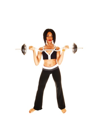 A nice slim woman in exercise outfit lifting weights, standing for whitebackground, barefoot  photo