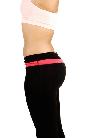 A picture of the butt of a young woman in black exercise pantsstanding in profile on white background  Stock Photo