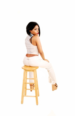 A beautiful young businesswoman sitting in white dress pants and vestin the studio for white background with her slim body and black hair  photo