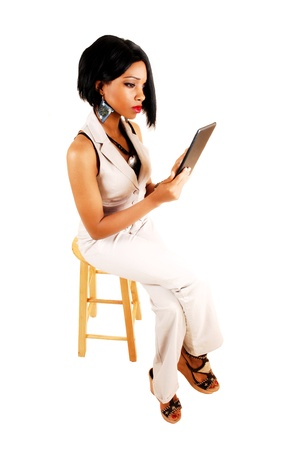 A serious young business woman sitting for white background in white dress pants and vest and black hair working with a tablet  photo