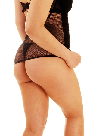 A young woman standing in black lingerie from the back, showing torsoand bottom for white background  photo
