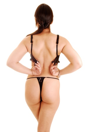 A young woman standing from the back for white background in a black thongclosing her bra  photo