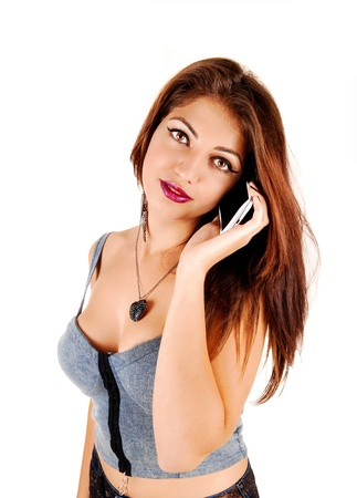 A young pretty woman with long brunette hair and a gray top talking on hercell phone for white background  photo