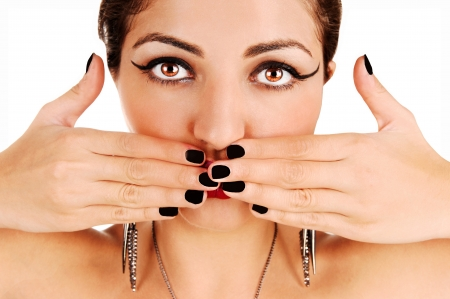 A pretty woman in closeup holding her fingers before her mouth, forwhite background  photo