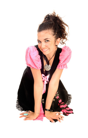 A lovely young woman kneeling on the floor, smiling, in a black and pinkcostume  photo