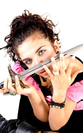A lovely young woman sitting and holding a sword in front of her face,looking serious photo