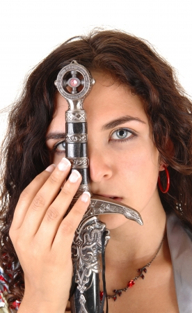 A closeup picture of a pretty woman holding a big sword in front of herface photo