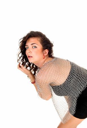 bending down: Una mujer joven que dobla hacia abajo, con una camisa de cota de malla de metal, mirando la c�mara intothe