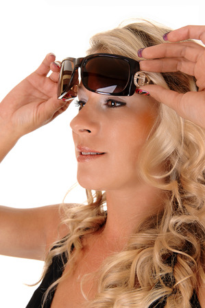 A closeup picture of a lovely blond woman holding her sunglasses above her eyes, closeup for white  photo