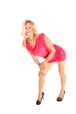 bending down: Una mujer delgada joven rubia en un vestido corto de color rosa y tacones altos standingfor fondo blanco y agacharse