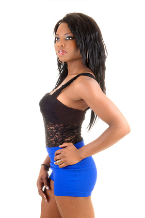 A young and pretty slim black woman standing in blue shorts and a blackcorset for white background  photo