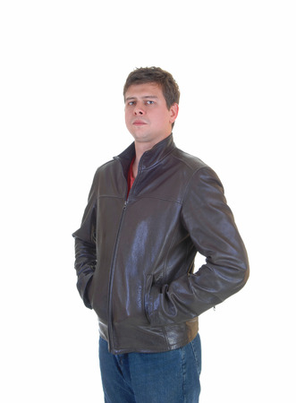 A young handsome man in a brown leather jacket and jeans standing  photo
