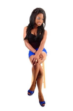 modelos negras: Una mujer delgada joven negro en pantalones cortos de color azul y un cors� negro sittingon una silla para el fondo blanco