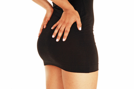 The bottom of a young woman in a short black dress standing in profilefor white background