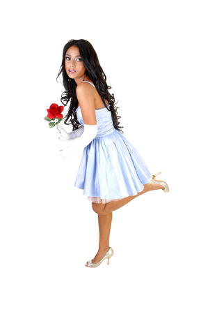 A sweet young Asian woman in a light blue dress, with a red rose in herhand, standing for white background  Stock Photo - 23820911