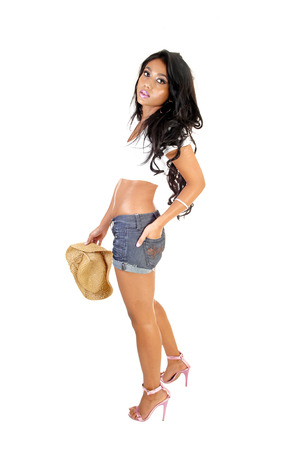 A lovely slim young Asian woman holding a beige straw hat in her hand,standing for white background  photo