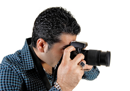 A young handsome man standing and taking pictures with his camerafor white background  photo