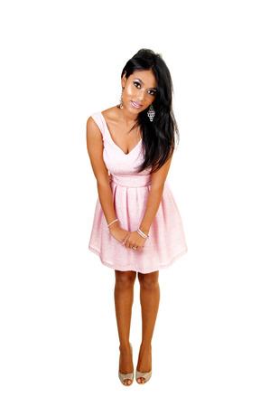bending down: Una joven mujer asi�tica en un vestido rosa de pie en el estudio de fondo forwhite e inclin�ndose