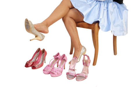 A closeup picture of a young woman sitting on a chair for white backgroundtrying on some high heels  photo