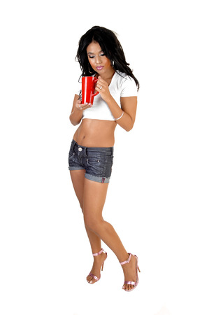 A very pretty young Asian woman with long black hair holding a red cupfor white background  photo