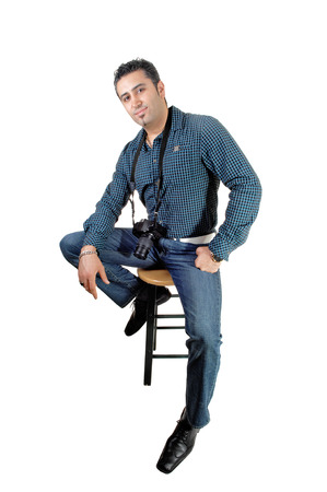 A young handsome man sitting on a chair with his camera around his neck,for white background  photo
