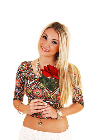 A lovely smiling young woman, holding a red rose in her hand, standingfor white background  photo