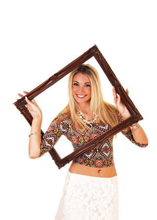 A smiling blond woman holding up a picture frame and looking trough,for white background  photo