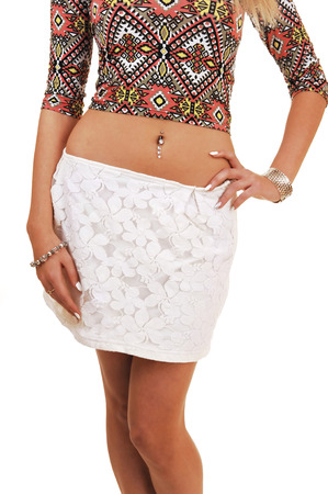A young slim woman standing from the front showing her stomach, in a white skirt for white background, as body part  photo