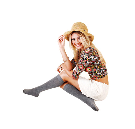 A lovely slim young girl crouching on the floor in a white skirt and colorful top in gray socks and beige straw hat, over white  photo