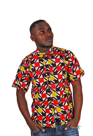 A handsome young black man in a colorful shirt and his hands in hispocket, looking up for white background  Stock Photo
