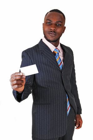 A young black business man standing in a suit and tie, holding up abusiness card for white background  photo