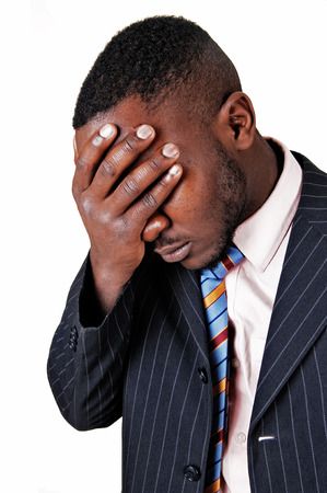 A closeup picture of a black man in a suit, holding his hand on his facefor sadness, for white background  photo