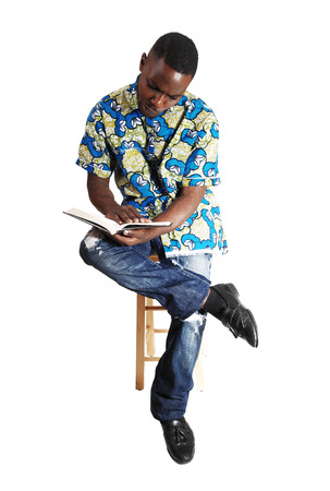A handsome young black man sitting and reading in a book, for whitebackground  photo