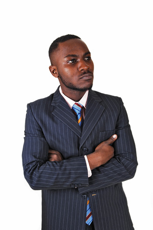 A young black business man standing in a suit and tie, holding up abusiness card for white background Stock Photo - 24822531