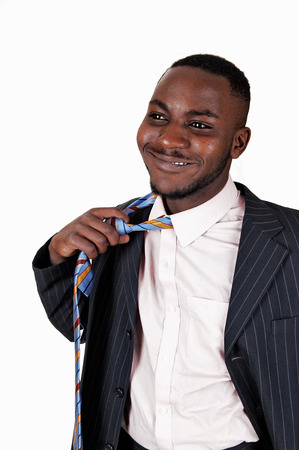 A smiling young black man taking off his necktie, in a suit forwhite background  photo