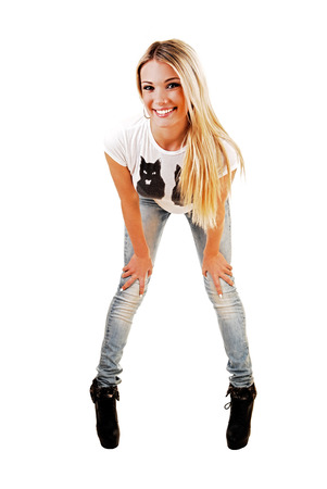 bending down: A slim young blond woman in jeans and white top standing in front, bending down