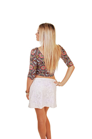 A beautiful blond woman in a white skirt and colorful top standing from the back Stock fotó