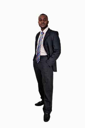 A young black business man standing in a suit and tie with his handsin his pocket for white background  photo